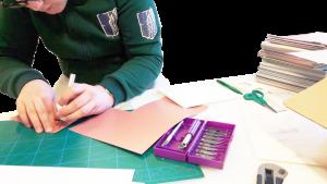 Pienoismallia varten värimallit leikattiin oikeaan kokoon ja muotoon pienoismalliveitsellä. Kuvan taustalla näkyy yli 500 värimallin nippu, jonka Tikkurila lahjoitti Arkkitehtuurikoulu Tiilille. Kuvassa työskentelee Roope Renko.